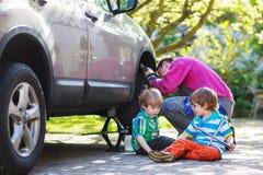 Engendre y dos niños pequeños que reparan el toge del coche y de la rueda de cambio Fotos de archivo libres de regalías