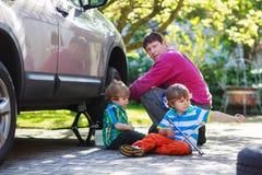 Engendre y dos niños pequeños que reparan el toge del coche y de la rueda de cambio Foto de archivo
