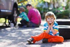 Engendre y dos niños pequeños que reparan el toge del coche y de la rueda de cambio Imagenes de archivo
