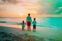 Engendre y dos niños que caminan en la playa en la puesta del sol foto de archivo
