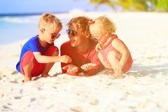 Engendre y dos niños que juegan con la arena en la playa Foto de archivo