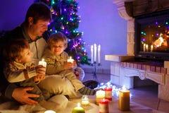 Engendre y dos pequeños niños pequeños que se sientan por la chimenea, las velas y la chimenea y mirando en el fuego Imagenes de archivo
