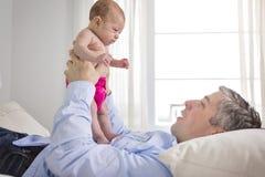 Engendre y es dos meses del bebé en cama en casa Imagen de archivo