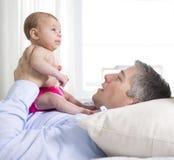 Engendre y es dos meses del bebé en cama en casa Fotografía de archivo
