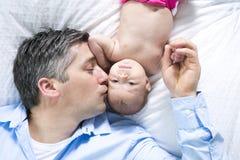 Engendre y es dos meses del bebé en cama en casa Fotos de archivo