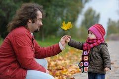 Engendre y su bebé en un parque del otoño Foto de archivo