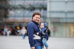 Engendre y su bebé en un portador de bebé imágenes de archivo libres de regalías