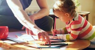 Engendre y su dibujo del hijo del bebé con los lápices coloreados en la sala de estar 4k almacen de metraje de vídeo