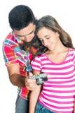 Engendre y su hija que mira imágenes en una cámara Fotos de archivo libres de regalías