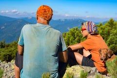 Engendre y su hijo adolescente con el perro divertido en montañas Foto de archivo