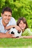 Engendre y su hijo con su bola en el parque Foto de archivo