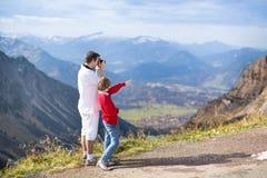 Engendre y su hijo que toma imágenes de mountais Fotografía de archivo