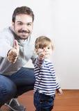 Engendre y su pequeña hija con los pulgares para arriba Imagen de archivo libre de regalías