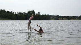 Engendre y su pequeña hija que se divierte en el lago almacen de metraje de vídeo