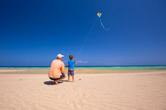Engendre y su pequeño hijo que juega con una cometa en la playa Imágenes de archivo libres de regalías