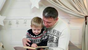 Engendre y su pequeño hijo que leía un libro junto, la familia que leía en casa, un padre y a un niño leyó una historia, un bueno almacen de metraje de vídeo
