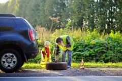 Engendre y su pequeño hijo que repara el coche y la rueda de cambio junto Imagen de archivo libre de regalías