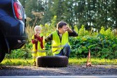 Engendre y su pequeño hijo que repara el coche y la rueda de cambio junto Fotos de archivo libres de regalías