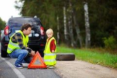 Engendre y su pequeño hijo que repara el coche y la rueda de cambio junto Foto de archivo libre de regalías