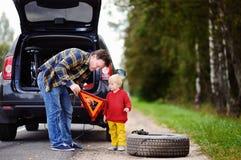 Engendre y su pequeño hijo que repara el coche y la rueda de cambio junto el día de verano Imágenes de archivo libres de regalías