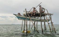 Engendre y sus dos hijas que se sientan fuera de su pequeña casa de la tienda que flota en el mar de Semporna, Sabah Semporna, Ma Fotografía de archivo