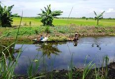 Engendre y sus dos niños a lo largo de un río Imagen de archivo
