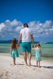 Engendre y sus dos niños que caminan por el mar Fotos de archivo