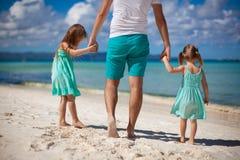 Engendre y sus dos niños que caminan por el mar Fotos de archivo libres de regalías