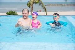 Engendre y sus niños que juegan en piscina al aire libre imagen de archivo libre de regalías