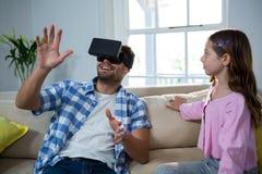 Engendrez à l'aide du casque de réalité virtuelle tandis que fille s'asseyant près de lui dans le salon Photographie stock