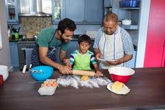 Engendrez aider le fils pour préparer la nourriture tout en se tenant prêt l'homme à l'aide du comprimé photos libres de droits