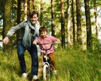 Engendrez apprendre son fils pour monter sur la bicyclette dehors image libre de droits