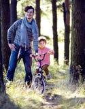 Engendrez apprendre son fils pour monter sur la bicyclette dehors en parc, sunn image stock