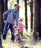 Engendrez apprendre son fils pour monter sur la bicyclette dehors en parc, sunn images stock