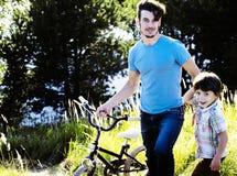 Engendrez apprendre son fils pour monter sur la bicyclette dehors, vrai f heureux photographie stock libre de droits