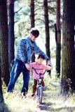 Engendrez apprendre son fils pour monter sur la bicyclette dehors, vrai f heureux photos libres de droits
