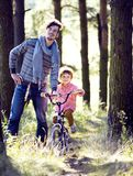 Engendrez apprendre son fils pour monter sur la bicyclette dehors, vrai f heureux images libres de droits