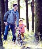 Engendrez apprendre son fils pour monter sur la bicyclette dehors, vrai f heureux photos stock