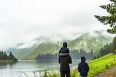Engendrez avec des enfants trimardant le long du lac beautlful avec la crique de collines images stock