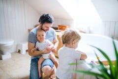 Engendrez avec deux enfants en bas âge étant prêts pour le bain dans la salle de bains à la maison image libre de droits
