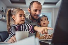 Engendrez avec deux enfants observant des bandes dessinées sur l'ordinateur portable photos libres de droits