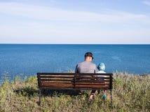 Engendrez avec l'enfant regardant à la mer devant la belle vue d'océan et de ciel Photo stock
