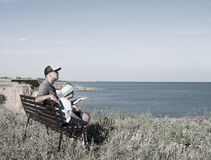 Engendrez avec l'enfant regardant à la mer devant la belle vue d'océan et de ciel Image libre de droits