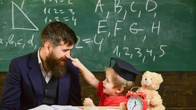 Engendrez avec la barbe, professeur enseigne le fils, petit garçon Badinez la gêne gaie tout en étudiant, déficit d'attention pro photos libres de droits