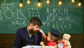 Engendrez avec la barbe, professeur enseigne le fils, petit garçon Badinez la gêne gaie tout en étudiant, déficit d'attention vil photo stock