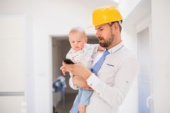 Engendrez avec la chemise, le lien, le casque et le smartphone tenant un fils de bébé à la maison Photos libres de droits