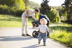 Engendrez avec la petite fille de fils et de bébé dans la poussette Parc ensoleillé Photo stock