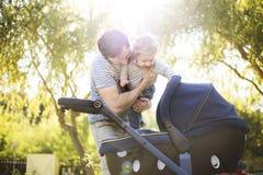 Engendrez avec la petite fille de fils et de bébé dans la poussette Parc ensoleillé Photographie stock
