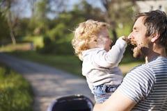 Engendrez avec la petite fille de fils et de bébé dans la poussette Parc ensoleillé Image stock