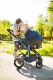Engendrez avec la petite fille de fils et de bébé dans la poussette Parc ensoleillé Photos libres de droits